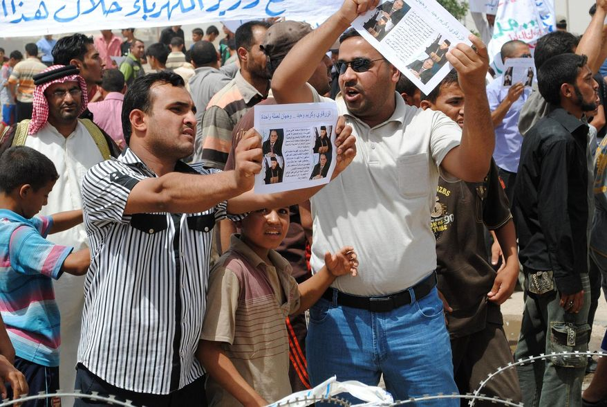 """A protester holds a flyer depicting Iraq's Electricity Minister Karim Waheed, top left, and Jordanian-born militant Abu Musab al-Zarqawi, bottom left, during a demonstration against electricity shortages in Nasiriyah, about 200 miles southeast of Baghdad, Iraq, Monday, June 21, 2010. Riot police in southern Iraq used water cannons to disperse protesters pelting them with stones Monday during a demonstration against power cuts as anger spread over the lack of basic utilities to fend off the country's searing summer heat. In Arabic, the flyer reads, """"Karim Waheed and Zarqawi are two sides of the same coin."""" (AP Photo)"""