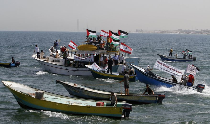 Palestinian and Lebanese flags wave over fishing boats off Gaza City, Gaza Strip, on Monday, June 21, 2010, during a demonstration supporting Lebanese ships planning to sail from Lebanon in an attempt to break the Israeli blockade of Gaza. (AP Photo/Adel Hana)