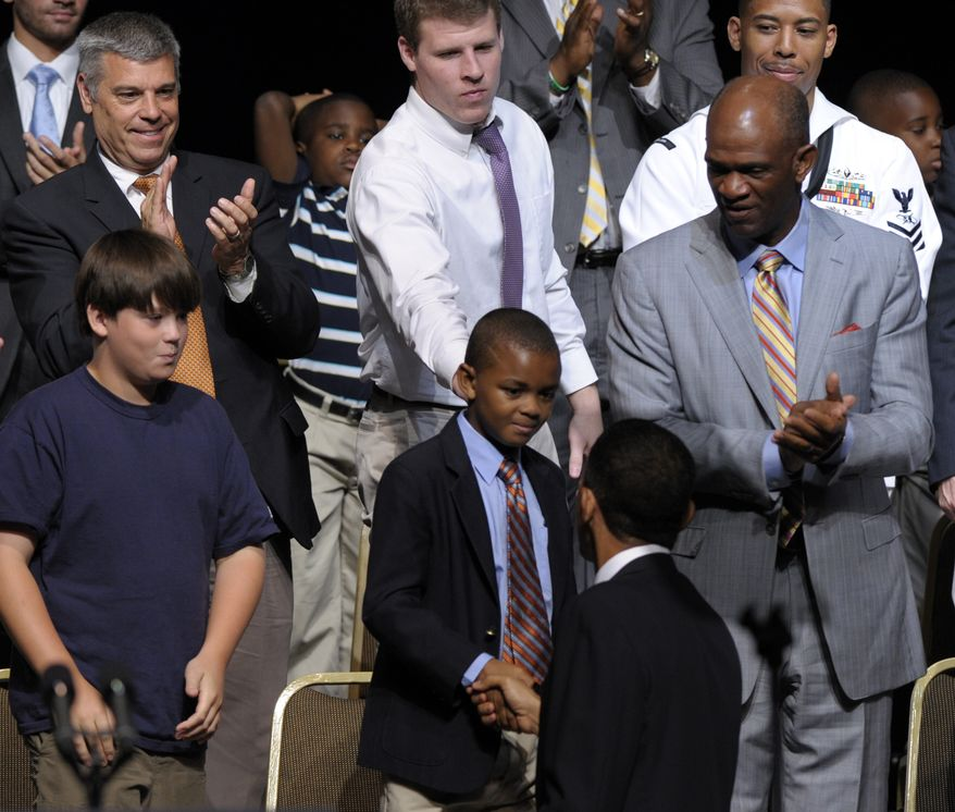 President Obama shakes hands with Alex Caldwell, 8, of Houston as his father, the Rev. Kirbyjon Caldwell (right) watches during a Father's Day event in Washington on Monday, June 21, 2010. (AP Photo/Susan Walsh)