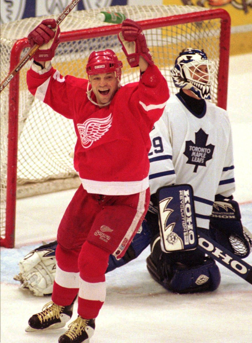 ASSOCIATED PRESS FILE - This March 19, 1996, file photo shows Detroit Red Wings' Dino Ciccarelli, left, celebrating a third-period goal by teammate Sergei Fedorov as Toronto Maple Leafs goalie Felix Potvin, right, looks to the scoreboard at Joe Louis Arena in Detroit. Ciccarelli, Cammi Granato and Angela James were elected to Hockey Hall of Fame, Tuesday June 22, 2010.