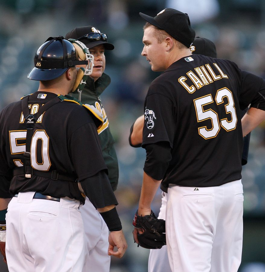 ASSOCIATED PRESS Oakland Athletics' Trevor Cahill, right, is visited on the mound by A's pitching coach Curt Young, center, and catcher Jake Fox  (50) during the sixth inning of a baseball game against the Minnesota Twins Saturday, June 5, 2010, in Oakland, Calif.