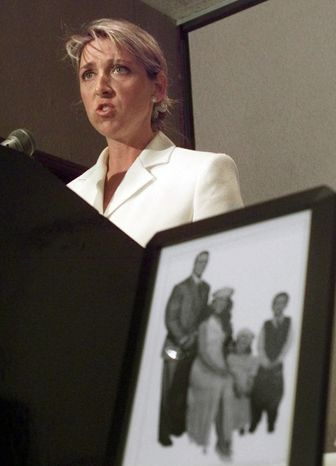 ** FILE ** In this June 15, 1999, photo, Martha Hart, widow of the professional wrestler Owen Hart, announces that her family has filed a wrongful-death lawsuit against the World Wrestling Federation in Kansas City, Mo., as a photo of the Harts and their two children sits in the foreground. (AP Photo/Cliff Schiappa, File)