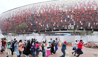 Food sellers protest their removal by police from outside the Soccer City Stadium construction site in Johannesburg in October. The group, dubbed the Soccer City Traders, was being shut down, the police said, because they had refused to make way for a new stage of construction, after selling food to construction workers for about two years. (Associated Press)