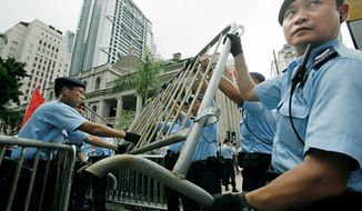 Police officers set up barriers outside the legislative chamber in Hong Kong on Tuesday. Hong Kong's Beijing-appointed leader on Wednesday asked the legislature to approve reforms with changes suggested by the pro-democracy camp. (Associated Press)