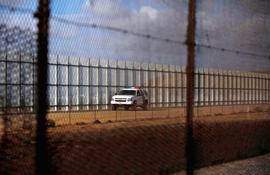 A U.S. Border Patrol agent patrols the U.S.-Mexico border fence in Tijuana, Mexico. The Border Patrol has quietly reduced its current force of available agents along the border because of cuts in the amount of overtime hours the agents can work. (Associated Press)