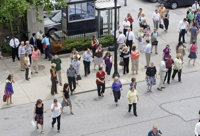 People make their way back into an office building in Cleveland after an earthquake shook parts of Canada and the United States on Wednesday, June 23, 2010. The magnitude-5.0 temblor, which was centered on the Ontario-Quebec border, cracked plaster in Cleveland and caused buildings to sway gently in Cincinnati. (AP Photo/Tony Dejak)