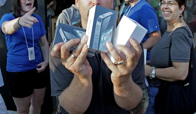 David Hill from Burleson, Texas, purchased three Apple iPhone 4s at the Apple Store in Fort Worth, Texas, on Thursday. Thousands lined up outside stores around the world to become among the first to own the device. (Associated Press)