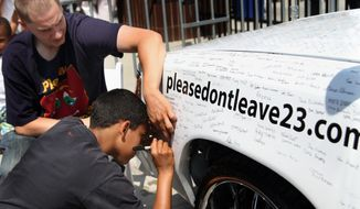 """Associated Press photographs Justin Blanks, 14, of Barberton, Ohio, signs Austin Briggs' 1987 Olds Cutlas Supreme during the """"LeBron Appreciation Day"""" in Akron, Ohio. Thousands of hometown fans gathered and were surprised when LeBron James, who did not commit to organizers to attend, walked through a side gate after the event officially ended."""