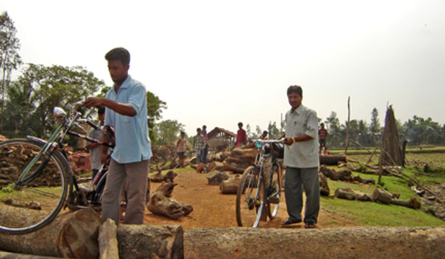 People protesting takeover of land for factories in Nandigram, India,  throw logs on the road to prevent entry of policemen.  (Sujoy Dhar/Special to The Washington Times)