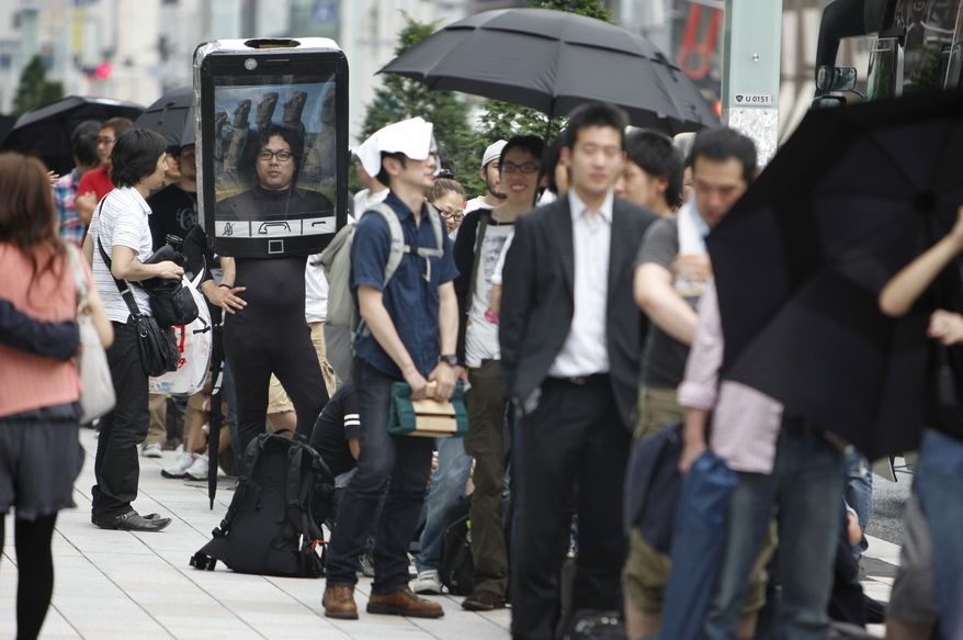 Customers line up to buy Apple's newest iPhone outside an Apple Inc's store at the Ginza district in Tokyo, Japan Thursday, June 24, 2010. Hundreds more lined up across the city at Apple stores and other Softbank outlets. (AP Photo/Shizuo Kambayashi)
