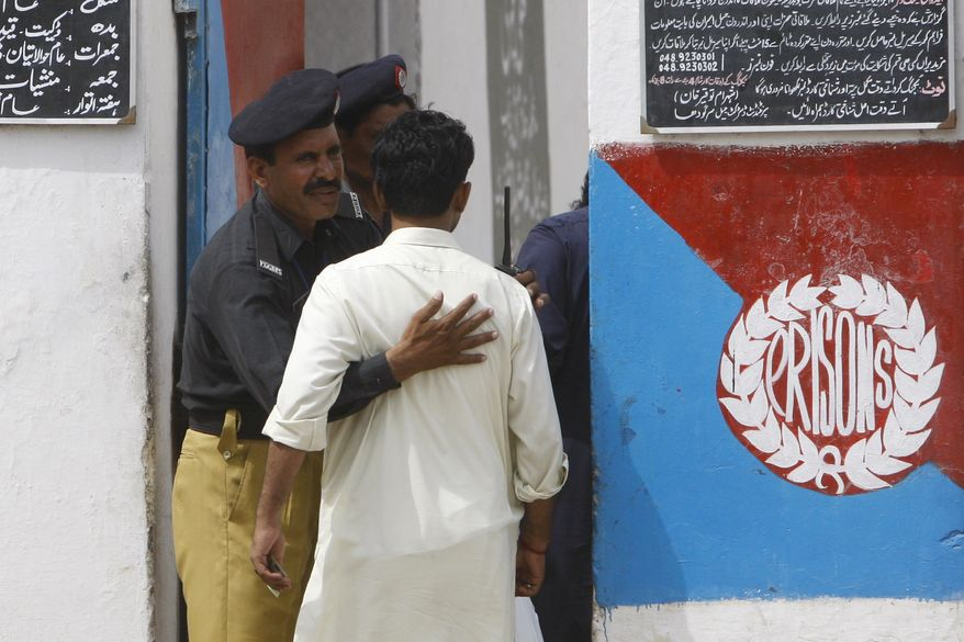 A Pakistani police officer frisks a man at the entrance of the district jail where five young Muslims from the Washington, D.C., area, who were arrested in Pakistan in December, are being held, in Sargodha, Pakistan, Thursday, June 24, 2010. (AP Photo/Dita Alangkara)