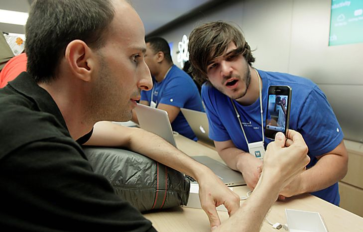 Robert Granoff, left, from New York, gets a tutorial about his Apple iPhone 4 from Anthony Farina at the Genius Bar in Apple's New York flagship store, Thursday, June 24, 2010. Apple Inc.'s newest iPhone was selling briskly Thursday as thousands lined up outside stores around the world to become among the first to own the device amid concerns of supply shortages.(AP Photo/Richard Drew)