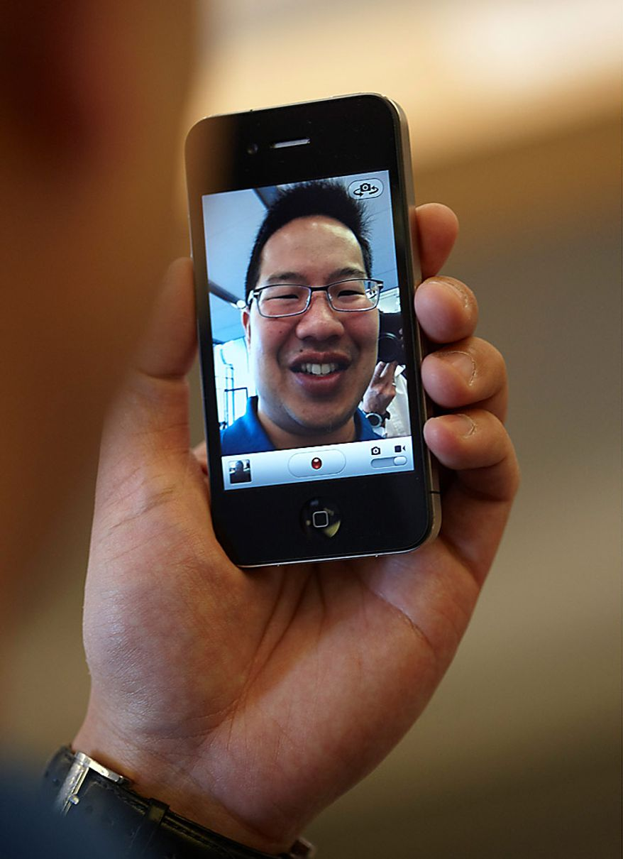 A customer uses the forward facing camera on an Apple Inc. iPhone 4 at an Apple store in London, U.K., on Thursday, June 24, 2010. Apple Inc. will probably sell a record 1 million iPhones today when the new version debuts and people such as John Whalen line up outside stores to be the first to buy it. Photographer Rupert Hartley/Bloomberg