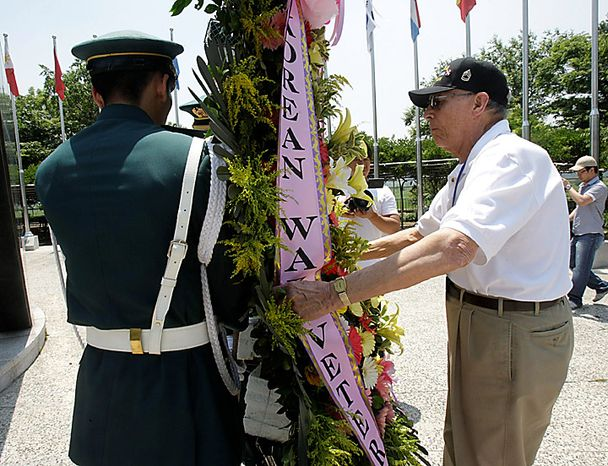 Robert James Cummiskey from Chesterfield, Missouri, a U.S. veteran who fought in the Korean War, right, carries a wreath of flowers with South Korean Army soldiers during a ceremony to mark the 60th anniversary of the Korean War at the Imjingak Pavilion in Paju near the border village of Panmunjom, the demilitarized zone that separates the two Koreas since the Korean War, north of Seoul, South Korea, on Thursday, June 24, 2010. During the war, the United States and 15 other countries fought alongside South Korea under the U.N. flag against North Korean and Chinese troops. (AP Photo/Ahn Young-joon)
