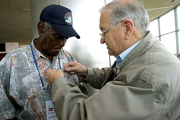 New Zealand Korean War veteran James Arthur Newman, right, pins a badge on Ethiopian Korean War veteran Habtemichael Genet on the eve of the 60th anniversary of the Korean War at an observation post in Paju near the border village of Panmunjom, the demilitarized zone that separates the two Koreas since the Korean War, north of Seoul, South Korea, on Thursday, June 24, 2010. The United States and 15 other countries fought alongside South Korea under the U.N. flag against North Korean and Chinese troops during the Korean War. (AP Photo/Ahn Young-joon)