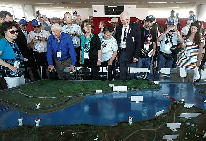 Foreign Korean War veterans and their family members look at a map of the two Koreas' borderland on the eve of the 60th anniversary of the Korean War at an observation post in Paju near the border village of Panmunjom, the demilitarized zone that separates the two Koreas since the Korean War, north of Seoul, South Korea, on Thursday, June 24, 2010. During the war, the United States and 15 other countries fought alongside South Korea under the U.N. flag against North Korean and Chinese troops. (AP Photo/Ahn Young-joon)