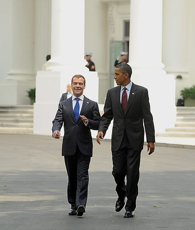 U.S. President Barack Obama (R) and Russian President Dmitry Medvedev walk from the North Portico of the White House on their way to the U.S. Chamber of Congress to discuss trade issues af