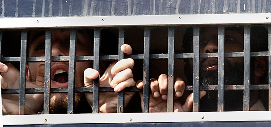 in a file photo, detained American Muslims shout from a prison van as they leave an anti terrorist court after their court appearance in Sargodha, Pakistan, Tuesday, March 2, 2010. The five American men were convicted Thursday on terror charges by a Pakistan court and sentenced to 15 years in prison each, a prosecutor said. The judge handed down two prison terms for each man, one for 10 years and the other for five, said deputy prosecutor Rana Bakhtiar. (AP Photo/Anjum Naveed)