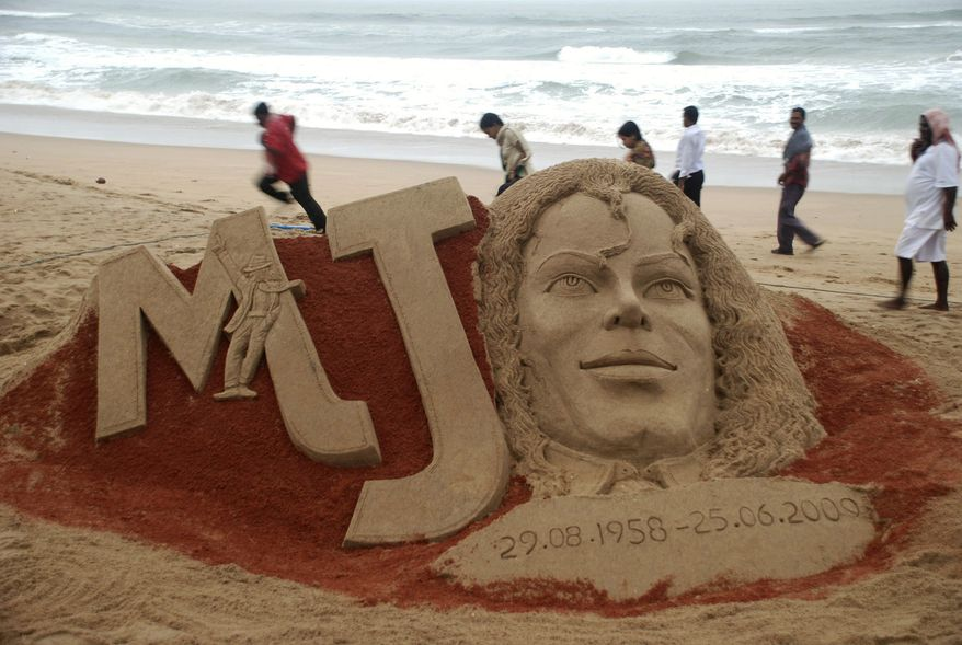 People walk past a sand sculpture of US performer Michael Jackson created to mark the first anniversary of his death, at the Bay of Bengal coast, in Puri, Orissa state, India, Thursday, June 24, 2010. (AP Photo)