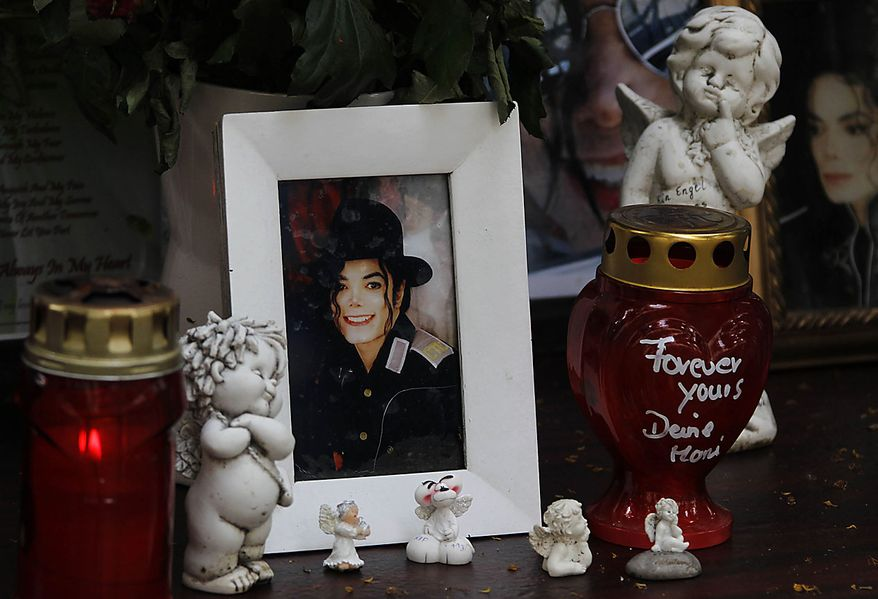 Candles and a picture of pop music icon Michael Jackson stands at a memorial in Munich, southern Germany, on Thursday, June 24, 2010. The death of Jackson, one year later, continues to captivate the world. (AP Photo/Matthias Schrader)