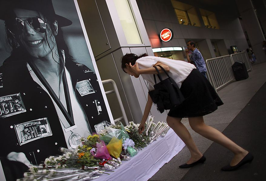** FILE ** A woman lays flowers at a makeshift memorial place ahead of the first death anniversary of King of Pop Michael Jackson in Tokyo, Friday, June 25, 2010. (AP Photo/Junji Kurokawa)