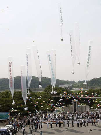 "South Korean conservative activists launch huge balloons carrying leaflets denouncing North Korean leader Kim Jong Il during a rally to mark the 60th anniversary of the Korean War at the Imjingak Pavilion in Paju near the border village of the Panmunjom (DMZ) that separates the two Koreas since the Korean War, north of Seoul, South Korea, Friday, June 25, 2010.  The two Koreas commemorated the anniversary Friday of the outbreak of the Korean War, promoting vastly different views of the origins of the conflict that still divides their peninsula a full six decades later. The letters on the balloons read "" Down with Kim Jong Il."" (AP Photo/Ahn Young-joon)"