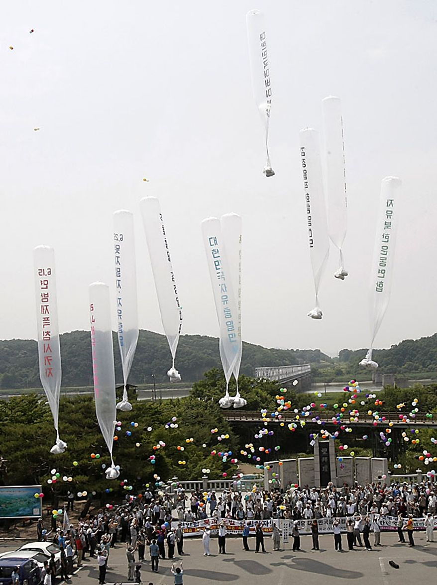 """South Korean conservative activists launch huge balloons carrying leaflets denouncing North Korean leader Kim Jong Il during a rally to mark the 60th anniversary of the Korean War at the Imjingak Pavilion in Paju near the border village of the Panmunjom (DMZ) that separates the two Koreas since the Korean War, north of Seoul, South Korea, Friday, June 25, 2010.  The two Koreas commemorated the anniversary Friday of the outbreak of the Korean War, promoting vastly different views of the origins of the conflict that still divides their peninsula a full six decades later. The letters on the balloons read """" Down with Kim Jong Il."""" (AP Photo/Ahn Young-joon)"""