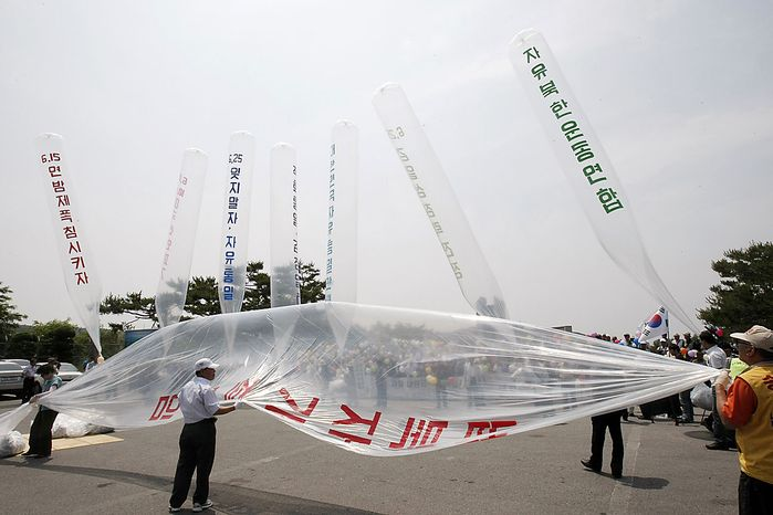 """South Korean conservative activists prepare to launch huge balloons carrying leaflets denouncing North Korean leader Kim Jong Il during a rally to mark the 60th anniversary of the Korean War at the Imjingak Pavilion in Paju near the border village of the Panmunjom (DMZ) that separates the two Koreas since the Korean War, north of Seoul, South Korea, Friday, June 25, 2010.  The two Koreas commemorated the anniversary Friday of the outbreak of the Korean War, promoting vastly different views of the origins of the conflict that still divides their peninsula a full six decades later. The letters on the balloons read """" Down with Kim Jong Il."""" (AP Photo/Ahn Young-joon)"""