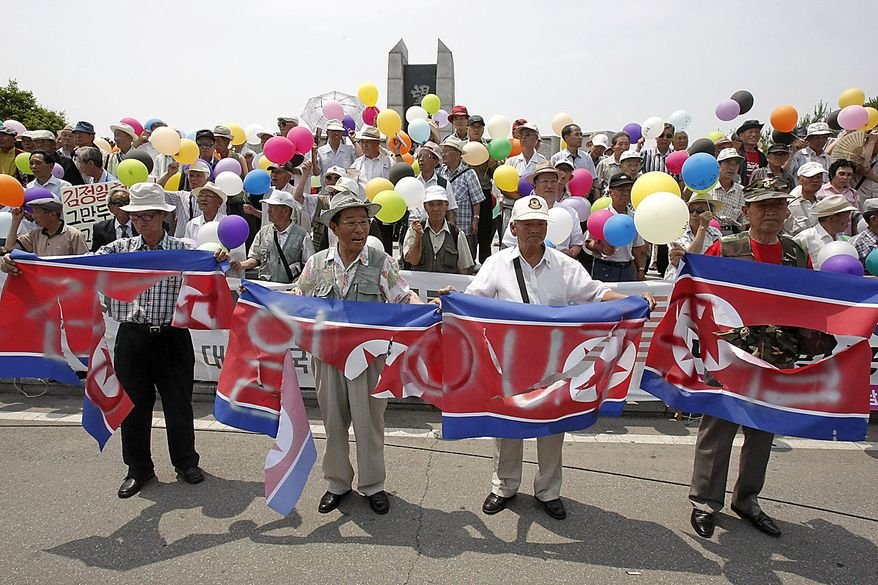 South Korean conservative activists with defaced North Korean flags stage a rally to mark the 60th anniversary of the Korean War at the Imjingak Pavilion in Paju near the border village of the Panmunjom (DMZ) that separates the two Koreas since the Korean War, north of Seoul, South Korea, Friday, June 25, 2010.  The two Koreas commemorated the anniversary Friday of the outbreak of the war, promoting vastly different views of the origins of the conflict that still divides their peninsula a full six decades later. (AP Photo/Ahn Young-joon)