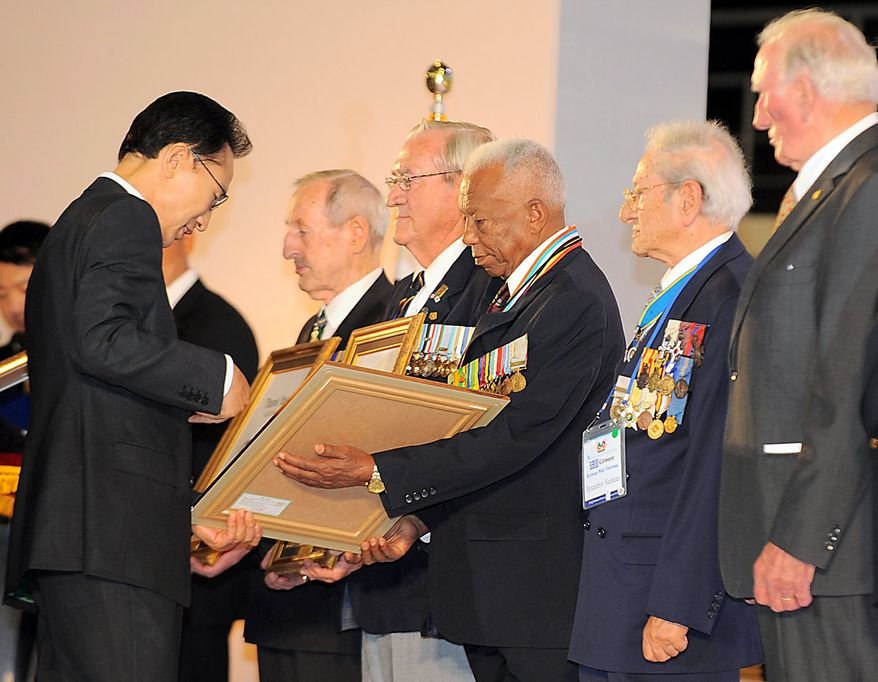 South Korea's President Lee Myung-bak, left, hands out citations to foreign veterans during a ceremony marking the 60th anniversary of the outbreak of the Korean War, at a gymnasium in Seoul, South Korea Friday, June 25, 2010. (AP Photo/Kim Jae-hwan, Pool)
