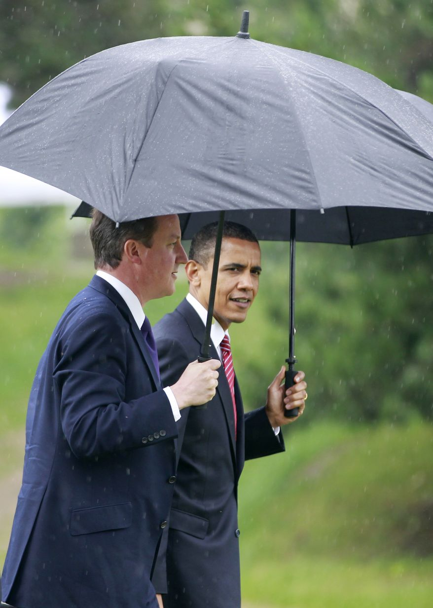 President Barack Obama and British Prime Minister David Cameron, left, walk in the rain after stepping off Marine One helicopter upon arrival in Toronto for the G-20 Summit, Saturday, June 26, 2010. (AP Photo/Charles Dharapak)