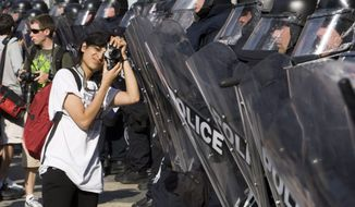 A protester takes pictures of riot police Friday, June 25, 2010 in Toronto. The leaders of the world's key industrialized nations have started to arrive for the G8 and G20 meetings which got underway Friday. (AP Photo/The Canadian Press, Ryan Remiorz)