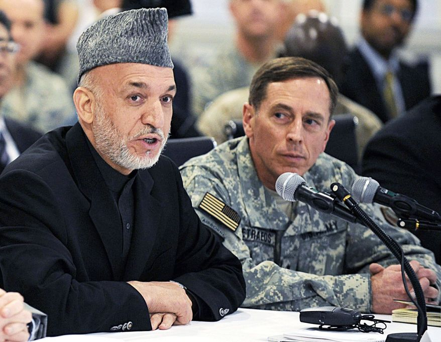 NEGOTIATING? Afghan President Hamid Karzai, here with U.S. Gen. David H. Petraeus in April, reportedly has met with al Qaeda-affiliated groups, perhaps about a government in Kabul. (Associated Press)