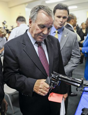 In this photo taken Aug. 13, 2009, Chicago Mayor Richard M. Daley looks at a handgun during a gun turn-in program in Chicago, as Chicago Police Superintendent Jody Weis looks on in the background. Daley, one of the nation's most vocal gun control advocates, said the city will not roll over if the Supreme Court rules against the city's gun ban. (AP Photo/Chicago Sun-Times, Rich Hein)