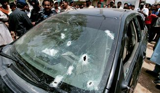 "Police officers and the public gather near a bullet-riddled car attacked by gunmen in Karachi. Close to half of the 600 murders reported so far this year have been ""target killings."" (Associated Press)"