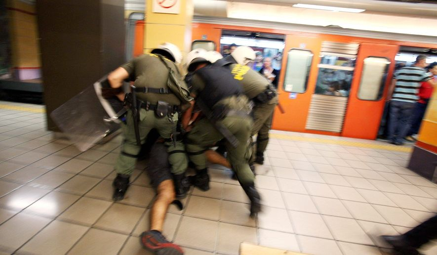 Riot police detain a man in an Athens subway station following clashes with demonstrators on Tuesday. Officers earlier dragged the man off a train and pepper-sprayed him. An estimated 16,000 people took part in two separate demonstrations. (Associated Press)