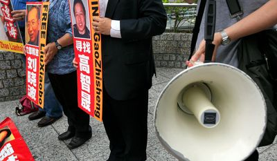 """Activists hold placards with Chinese words that say """"release Liu Xiaobo and Gao Zhisheng"""" during a protest outside the U.S. consulate in Hong Kong in May as they demand the Chinese government to release the political prisoners who are in urgent health conditions. This week's resumption of U.S.-China human rights talks after two years will spotlight what critics say is a deterioration in Beijing's record on legal protections, free speech and civil society, and are expected to take up individual cases such as Liu Xiaobo's, along with a list of topics including religious freedom, attacks on the legal profession and China's strict Internet controls. (Associated Press)"""