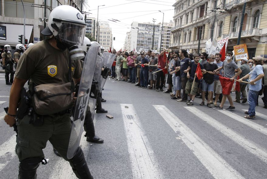 Protesters chant slogans next to a riot police cordon during clashes at a union protest in Athens on Tuesday, June 29, 2010. (AP Photo/Petros Giannakouris)