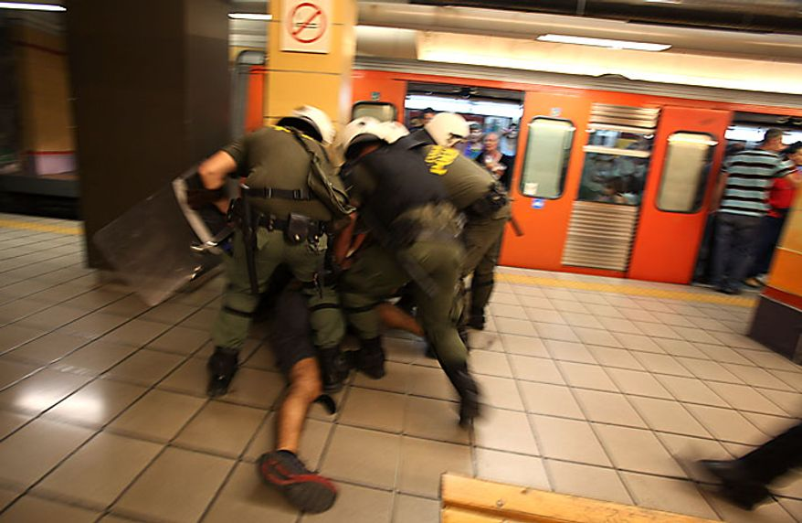 Riot police detain a young man in an Athens metro station following clashes with demonstrators on Tuesday, June 29, 2010. Officers earlier dragged the suspect off a train and sprayed him with pepper gas. Some 16,000 people took part in two separate demonstrations, the second of which turned violent as stone-throwing youths fought with riot police. (AP Photo)