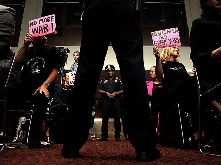 Capitol Police officers stand in front of protesters seated in the audience on Capitol Hill in Washington, Tuesday, June 29, 2010, as Gen. David Petraeus testified before the Senate Armed Services Committee hearing to be confirmed as President Obama's choice to take control of forces in Afghanistan. (AP Photo/Pablo Martinez Monsivais)