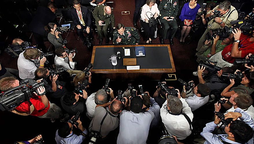 Photographers gather around Gen. David Petraeus as he gives a thumbs-up, on Capitol Hill in Washington, Tuesday, June 29, 2010, prior to his testifying before the Senate Armed Services Committee to be confirmed as President Obama's choice to take control of forces in Afghanistan. (AP Photo/Pablo Martinez Monsivais)