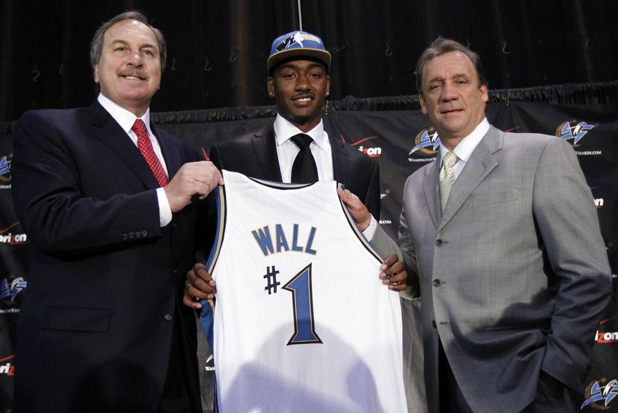 ASSOCIATED PRESS Washington Wizards first draft pick John Wall, center, from the University of Kentucky, smiles as he holds up a jersey with coach Flip Saunders, right, and Wizards president Ernie Grunfeld during a news conference in Washington, on Friday, June 25, 2010. Wall was selected as the No. 1 overall pick in the NBA basketball draft on Thursday.
