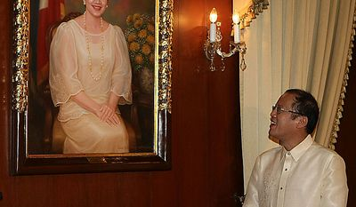 New Philippine President Benigno Aquino III looks at a portrait of his late mother, former President Corazon Aquino, at the presidential palace in Manila, Philippines, Wednesday, June 30, 2010. Aquino was sworn in Wednesday as the Philippines' 15th president, leading a Southeast Asian nation his late parents helped liberate from dictatorship and which he promises to deliver from poverty and pervasive corruption. (AP Photo/Rolex dela Pena, Pool)