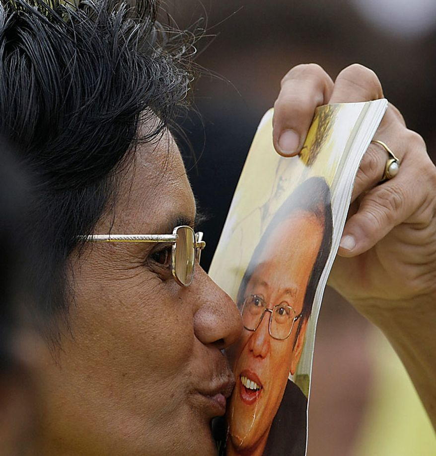 A supporter kisses a picture of Benigno Aquino III during his inauguration ceremony Wednesday, June 30, 2010 at the Quirino grandstand in Manila, Philippines. Aquino was sworn in as the country's 15th president to lead a Southeast Asian nation his late parents had helped liberate from a dictatorship and which he now promises to deliver from poverty and pervasive corruption. (AP Photo/Pat Roque)