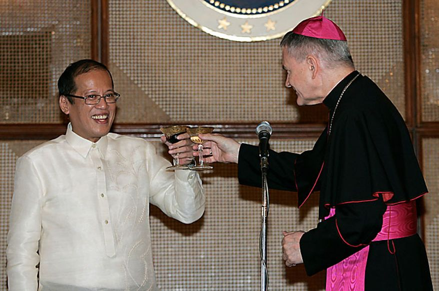 The Philippine's new President Benigno Aquino III, left, toasts with Papal Nuncio to the Philippines Archbishop Edward Joseph Adams during his inaugural reception at the Malacanang presidential palace in Manila, Philippines on Wednesday June 30, 2010. (AP Photo/Aaron Favila, Pool)
