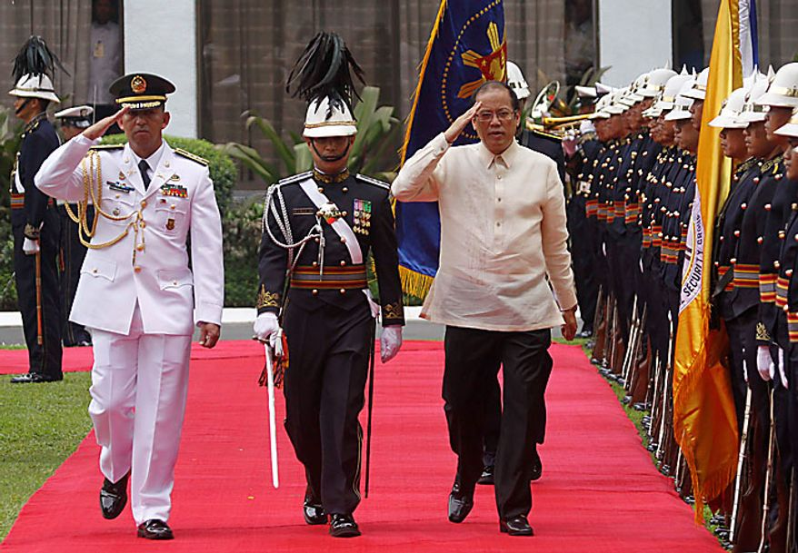 Newly inaugurated Philippine President Benigno Aquino III, center right, salutes military honors upon his arrival at the Malacanang presidential palace in Manila, Philippines on Wednesday June 30, 2010. (AP Photo/Aaron Favila, Pool)