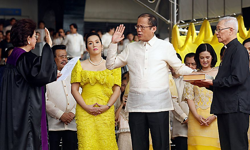 Benigno Aquino, Philippine president, second right, is sworn in by Associate Justice Conchita Carpio Morales, left, at Quirino Grandstand in Manila, the Philippines, on Wednesday, June 30, 2010. Aquino, who rose from political outsider to Philippine president in less than a year, takes office today pledging to fight poverty, narrow the budget deficit and refrain from raising taxes in a nation trailing its neighbors in economic growth and international investment. Photographer: Edwin Tuyay/Bloomberg