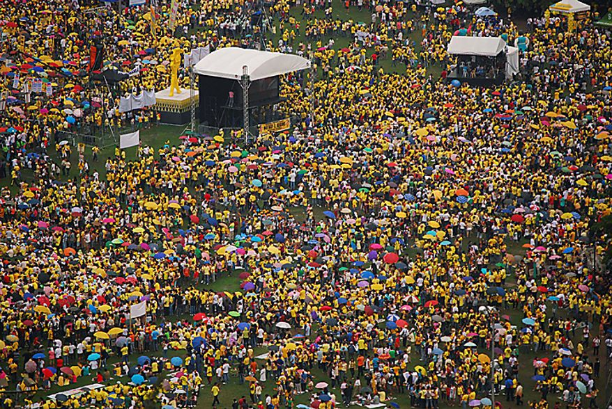 People gather at Rizal Park to witness the oath-taking ceremony of Benigno Aquino III as the Philippines' 15th President Wednesday, June 30, 2010 in Manila, Philippines. (AP Photo)