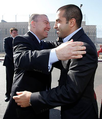 Mosab Hassan Yousef, right, is hugged by former Israeli security service agent Gonen Ben-Itzhak, after his deportation hearing at the immigration detention center in San Diego, Wednesday, June 30, 2010. A U.S. immigration judge in San Diego has agreed to grant asylum to Yousef. (AP Photo/Denis Poroy)