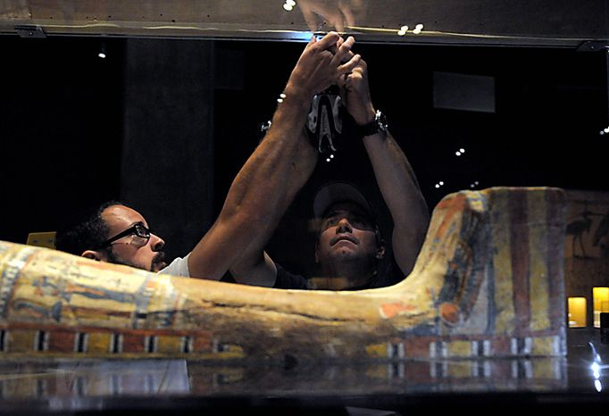 In this June 28, 2010 photo, Eric Rossi and John Diloszycki close the case on an Egyptian sarcophagus and mummy in Los Angeles in preparation for the opening of the new Mummies of the World exhibit at the California Science Center. The 45 mummies and 95 artifacts in the show come from 15 museums in seven countries, said Marc Corwin, CEO of American Exhibitions Inc. The show opens Thursday at the California Science Center, then will go on a three-year tour across the country. (AP Photo/Adam Lau)